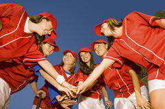Softball Players Stacking Hands Against Blue Sky. Happy female softball players stacking hands against clear blue sky Royalty Free Stock Photos