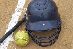 Softball scene. A bat, softball and helmet on the infield Royalty Free Stock Images
