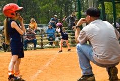 Softball-Seitentrieb und Trainer des Mädchens Stockfotografie