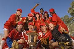 Softball Team And Coach With Trophy Celebrating Against Sky. Low angle portrait of successful female softball team and coach with trophy celebrating against blue Stock Image