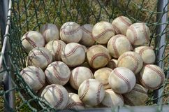 A net full of softballs sit ready for a softball game royalty free stock photo