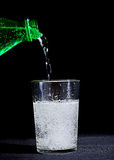 Glass of Softdrink water. Water pouring in a glass with black background at the table stock photos