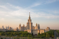 Soften edge view of sunset Moscow university framed with green trees under cloudy sky Royalty Free Stock Photography