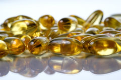 Softgel capsules on reflective surface Stock Photography