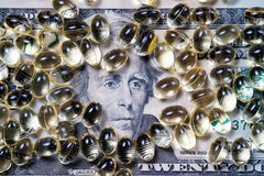 Softgel capsules on US currency background Royalty Free Stock Image