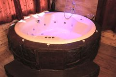Softly Lit Jacuzzi. A softly lit jacuzzi hot tub in a romantic wood cabin Royalty Free Stock Photos