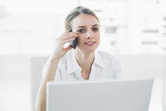 Softly smiling businesswoman sitting at her desk while phoning Stock Photos