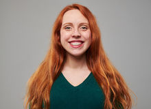 Softly smiling young woman with red hair posing at the royalty free stock image