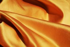 Softness of texture, background. The close image of the golden fabric reveals its soft texture generating the caloric feeling of heat Royalty Free Stock Photography