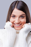 Softness and warmness. Close-up of young woman in white sweater holding hands near face and smiling while standing against grey background Stock Images