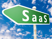 Software as a Service. SaaS - Software as a Service - street sign illustration in front of blue sky with clouds Stock Images