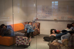 Software developers sleeping on sofa in creative startup office Stock Photo