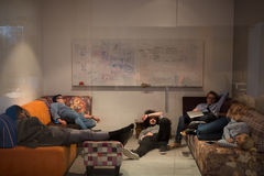 Software developers sleeping on sofa in creative startup office Stock Photography