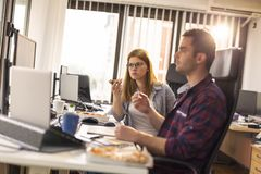 Software developers taking a lunch break. Two software developers on a lunch break in an office, drinking coffee and eating pizza. Focus on the woman Royalty Free Stock Photos