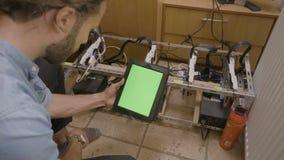 Software Engineer que verifica o processo de mineração na posição verde chave da tela do croma da tabuleta ao lado da máquina de  video estoque