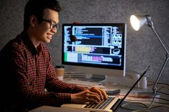 Software engineer working on project. Cheerful Asian software engineer enjoying working on project all night long royalty free stock photography