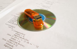 Software engineering concept. Close up image of cd disc and a flash drive, over white sheets of source code stock image