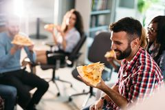 Software enginneers sharing pizza on break from work Royalty Free Stock Image