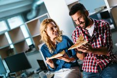 Software enginneers sharing pizza on break from work Stock Photos