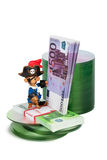 Software piracy. Pirat toy with bundle of money and cd disks concept of software piracy Stock Photography