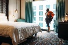 Soggiorno del viaggiatore di viaggiatore con zaino e sacco a pelo della donna nella camera di albergo di alta qualità Fotografia Stock