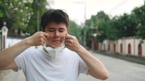 Soggiorno dell'uomo dell'Asia accanto ed indossare maschera N95 per proteggere cattivo inquinamento PM2 la polvere 5 nel giovane  video d archivio