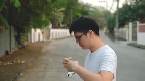 Soggiorno dell'uomo dell'Asia accanto ed indossare maschera N95 per proteggere cattivo inquinamento PM2 polvere 5 in città stock footage