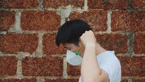 Soggiorno dell'uomo dell'Asia accanto ed indossare maschera N95 per proteggere cattivo inquinamento PM2 polvere 5 con il fondo de stock footage