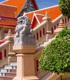 Soggiorno della statua del leone del granito davanti al tempio tailandese Immagine Stock Libera da Diritti
