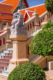 Soggiorno della statua del leone del granito davanti al tempio tailandese Fotografie Stock