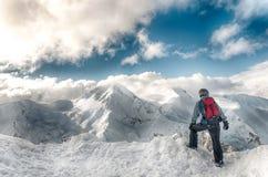 Soggiorno dello sciatore con gli sci su grande roccia sul contesto delle montagne Bansko, Bulgaria immagine stock