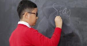Soggiorno di scrittura dello studente maschio in testo di scuola stock footage