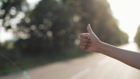 Soggiorno di Womaan alla strada con il pollice su nel giorno soleggiato di estate Fine in su hitchhiking viaggiatore trasporto stock footage