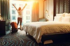 Soggiorno felice del viaggiatore di viaggiatore con zaino e sacco a pelo nell'hotel di alta qualità immagini stock