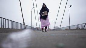 Soggiorno senza tetto adulto della donna sul ponte vicino al porto fluviale in tempo grigio ventoso freddo che chiede l'aiuto e c video d archivio
