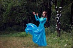 Sogna la giovane donna in vestito blu nella foresta Fotografie Stock