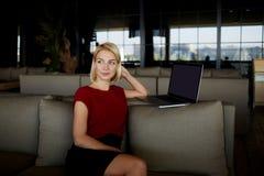 Sognando la donna che si siede in computer portatile vicino interno del ristorante con la copia spazi lo schermo per il vostro me Immagine Stock Libera da Diritti
