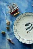 Sogni del mare e del viaggio, un piatto con un pallone, coperture, una nave di legno Su una tela degli azzurri fotografie stock