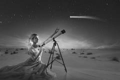 Sogni della giovane donna, concetto La ragazza esamina una cometa o la stella cadente utilizza un telescopio Fondo del deserto, fotografia stock