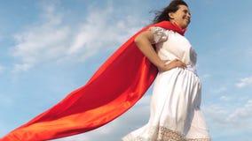 sogni della ragazza di trasformarsi in un supereroe condizione sexy sul campo in un mantello rosso, mantello della ragazza del su video d archivio