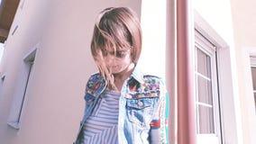 sogni della ragazza vestiti variopinti di bei di un giorno soleggiato della casa Fotografia Stock