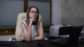 Sogni di segretario della donna di un posto di lavoro in un ufficio Pensiero della ragazza, sedentesi alla tavola archivi video
