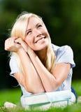Sogni sorridenti della ragazza che si trovano sull'erba Immagini Stock