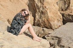 Sogno della ragazza bella che si siede sulle grandi pietre Immagini Stock Libere da Diritti
