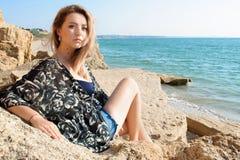 Sogno della ragazza bella che si siede sulle grandi pietre Fotografie Stock