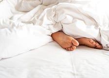 Sohle des Frauenfußes in der unordentlichen Decke auf Bett Weißes Kissen mit Querstation stockfotografie
