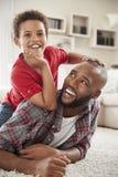 Sohn-Aufstiege auf Vätern ziehen zurück sich, während sie Spiel im Aufenthaltsraum zusammen spielen lizenzfreie stockfotografie