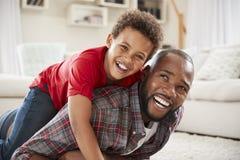 Sohn-Aufstiege auf Vätern ziehen zurück sich, während sie Spiel im Aufenthaltsraum zusammen spielen stockfotos