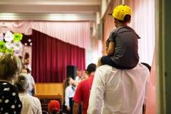 Sohn, der auf den Schultern seines Vaters sitzt stockfotografie