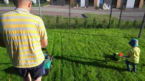 Sohn, der einen SpielzeugRasenmäher drückt, während Vati mit seinem mäht Kardanringschu? stock video footage